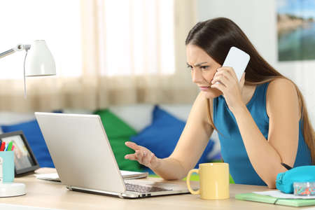 노트북을보고 집안에 그녀의 침실에서 고객 서비스와 전화 상담 화가 난 학생