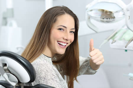 Patient with perfect white teeth and smile satisfied after dental treatment in a dentist office with medical equipment in the background Banco de Imagens