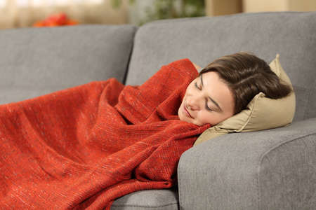 Portrait of a girl sleeping covered with an orange blanket lying on a comfortable couch in the living room at home Stock Photo