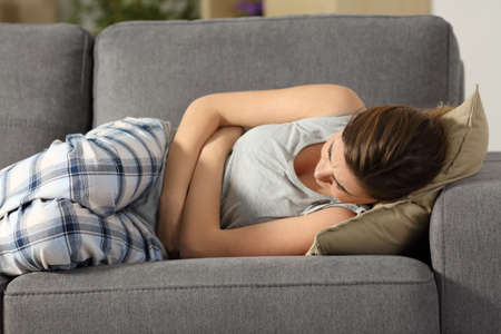 Teen suffering belly pms symptoms lying on a sofa in the living room at home Stock Photo