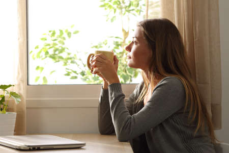 Side view of a relaxed woman looking through a window sitting in a table and holding a cup of coffee at home