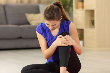 家庭的な背景付きのリビング ルームの床の上に座って膝の痛みに苦しんでいるスポーツウーマン