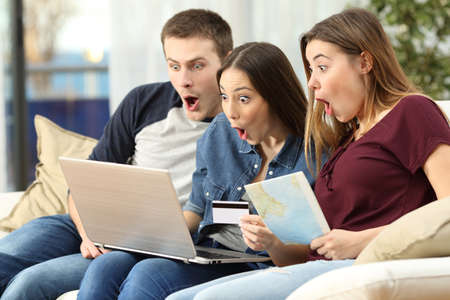Three amazed friends finding trip offers on line with a laptop sitting on a couch in the living room in a house interior Stockfoto