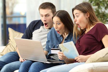Tres amigos sorprendidos encontrar ofertas de viaje en línea con un ordenador portátil sentado en un sofá en la sala de estar en un interior de la casa Foto de archivo