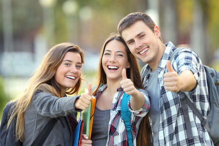 Three happy students looking at you with thumbs up in an university campus Stockfoto