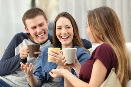 Three happy friends talking and laughing loud holding drinks sitting on a sofa in the living room at home