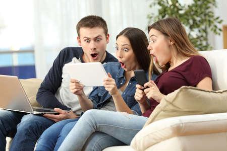 Drie verbaasde vrienden op lijn met meerdere apparaten die op een bank in de woonkamer in een huisinterieur zitten