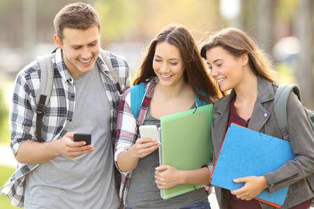 대학 캠퍼스 야외에서 스마트 폰 확인 세 행복 학생 스톡 콘텐츠