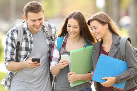 Three happy students checking smart phones outdoors in an university campus