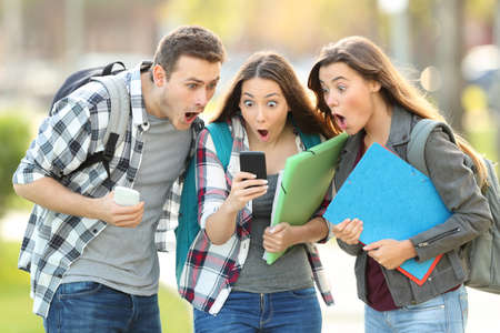 Three amazed students checking on line content on a smart phone in the street Foto de archivo