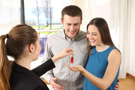 Gelukkig paar die de sleutels van hun nieuw leeg huis in de woonkamer ontvangen na het kopen Stockfoto