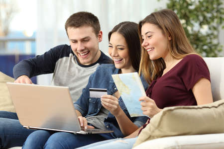 Drie vrienden plannen en kopen een reis op lijn met een creditcard en een laptop op een bank in de woonkamer thuis