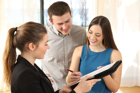 Happy couple signing contract after buying a new house