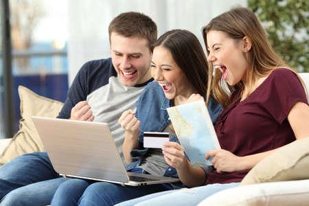 Drie opgewonden vrienden kopen een reis op lijn met een creditcard en een laptop op een bank in de woonkamer thuis