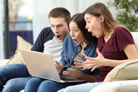 Three amazed friends watching media content on line in a computer sitting on a couch in the living room at home Фото со стока