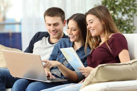 Drie vrienden plannen een reis met een laptop en een papieren kaart op lijn zitten op een bank in de woonkamer thuis