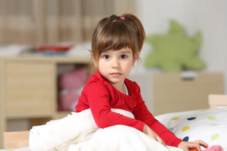 attentive: Portrait of a beautiful toddler girl looking at you sitting on the bed in her bedroom at home