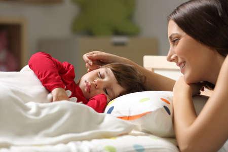 Orgullosa madre mirando para dormir en la cama a su hija en un dormitorio en casa Foto de archivo