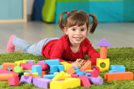 Toddler girl posing and looking at you lying on the floor with a lot of toys in her room