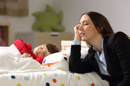 Tired worker mother wearing suit sleeping beside her sleepy daughter on a bed at home