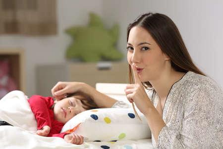 母の家のインテリアで寝室のベッドで眠っている彼女の幼児で沈黙を求め