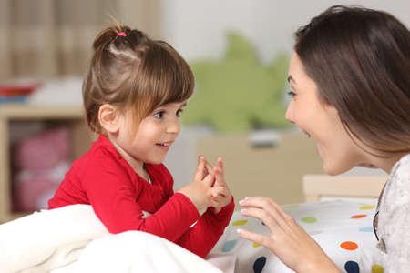 Madre y niño con camisa roja jugando juntos en una cama en el dormitorio en casa Foto de archivo - 80623428