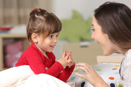 Mother and toddler wearing red shirt playing together on a bed in the bedroom at home Stock Photo