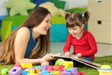 Moeder en peuter spelen samen met een boek op de vloer in de slaapkamer thuis met een kleurrijke achtergrond Stockfoto