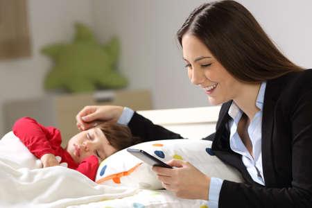Werker moeder die aan de lijn werkt en een slimme telefoon houdt terwijl haar peuter in een bed in haar slaapkamer thuis slaapt Stockfoto
