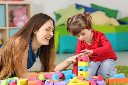 Madre e hija jugando junto con juguetes de construcción de colores en una alfombra en el piso af un dormitorio en casa Foto de archivo