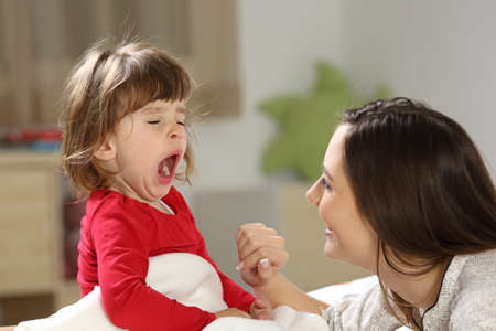 Portrait of a toddler yawning after nap on a bed beside her mother with a bedroom in the background