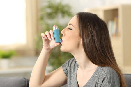 Side view of an asthmatic woman using an inhaler sitting on a couch in the living room at home Foto de archivo