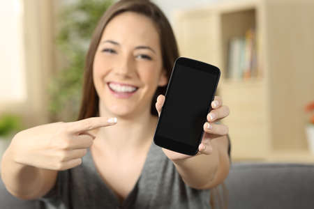 front house: Front view of a girl pointing and showing a blank phone screen looking to you sitting on a sofa in the living room at home
