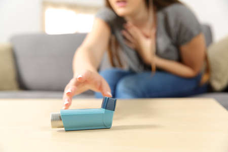 Girl suffering asthma attack reaching inhaler sitting on a couch in the living room at home 스톡 콘텐츠
