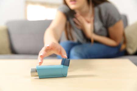 Une fille souffrant d'une crise d'asthme atteignant un inhalateur assis sur un canapé dans le salon à la maison Banque d'images