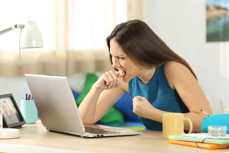 molesto: Estudiante enojado con un fallo de portátil sentado en un escritorio en su habitación en un interior de la casa con una ventana en el fondo