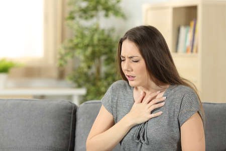 집에서 거실에서 소파에 앉아 호흡 문제를 겪고 여자