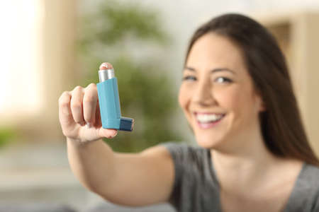Chica mostrando un inhalador de asma sentado en un sofá en la sala de estar en casa Foto de archivo