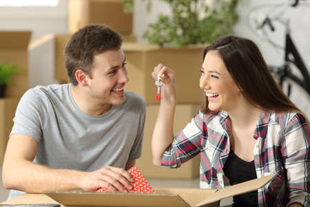 Casual couple unpacking belongings and showing keys sitting on the floor of the loving room in their new house with boxes in the background Foto de archivo