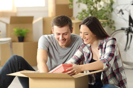 Happy casual couple sitting on the floor unpacking a box while moving house  in the living room Stock Photo