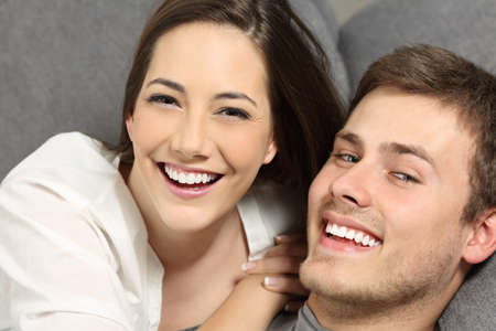 Happy couple with perfect teeth and white smile lying on a couch and looking at you