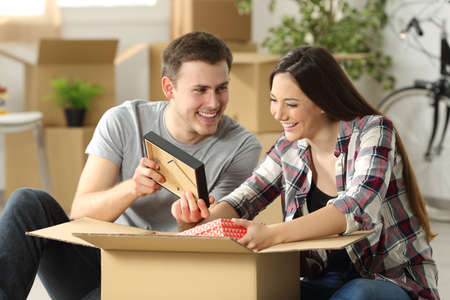 Happy casual couple moving house and remembering moments sitting on the floor while packing belongings in a carton box
