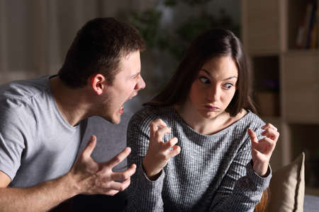 Couple arguing and shouting sitting on a couch in the living room at home with a dark background