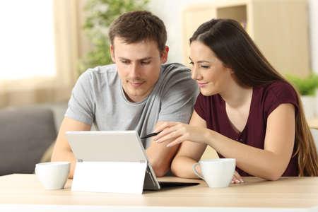 Pareja buscando en línea contenido con una tableta pc sentado en una mesa en la sala de estar en casa con una ventana en el fondo