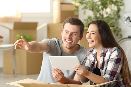 Feliz pareja mudarse juntos planeando en línea con una tableta sentada en el suelo en casa con cajas en el fondo