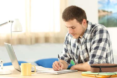 그의 방에있는 책상에서 숙제를하는 노트북에 쓰는 학생의 초상화 스톡 콘텐츠