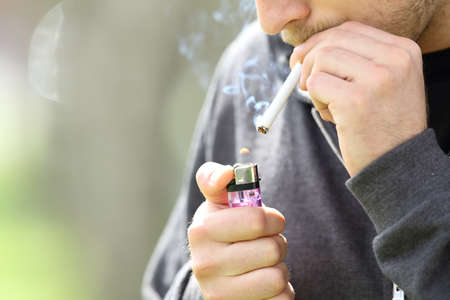 Close up of a teen hands holding a lighter lighting a cigarette ready to smoke
