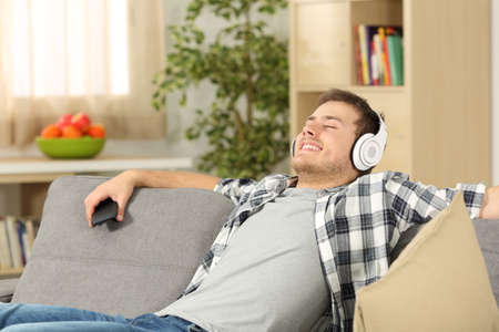 Single casual man with eyes closed listening to music on line from a smart phone sitting on a sofa in the living room in a house interior