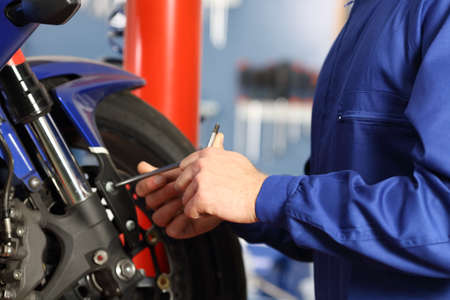 Motorbike mechanic hands disassembling parts in a workshop with equipment in the background Stock Photo