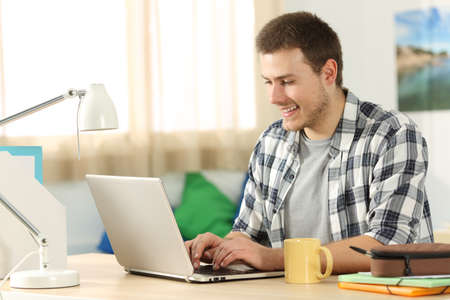 Happy student writing in a laptop sitting on a desk in his room